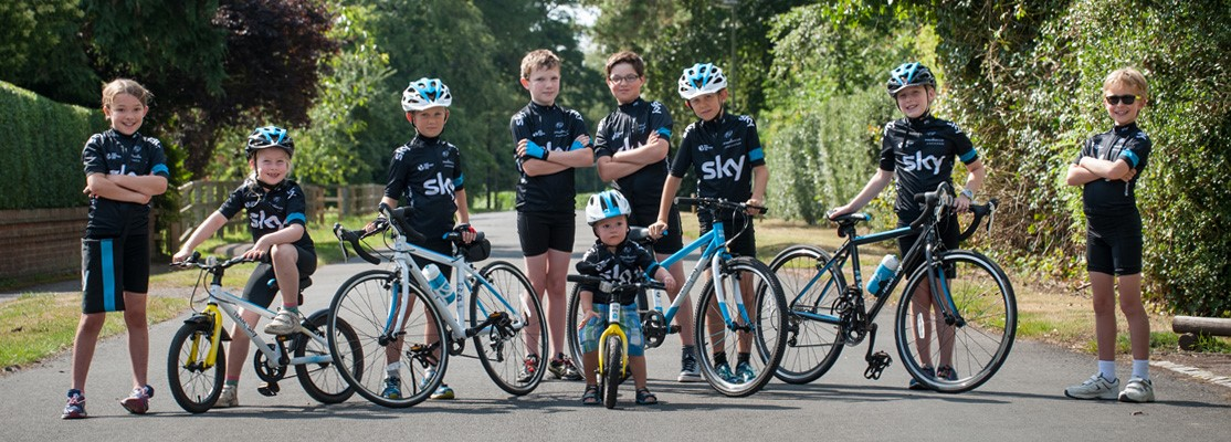 Children riding Frog Team Sky bikes with matching team kits
